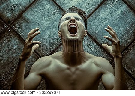 Pain. Art portrait of a naked muscular man who screams on a dark grunge background. Emotions.