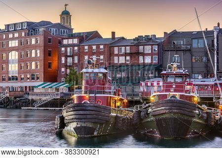 Portsmouth, New Hampshire, USA town cityscape with tugboats in the morning.