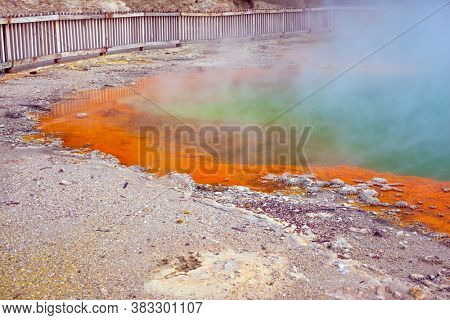 Hot lake with gas bubbles and orange shore. The geothermal zone of Rotorua. Thermal Wonderland Champagne. Wai-O-Tapu, New Zealand. The concept of exotic, ecological and photo tourism