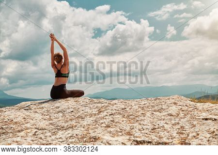 Female Sitting In Stylish Outfit. Lady Meditating On Nature. Pilates Or Stretching Concept. Yoga Tim