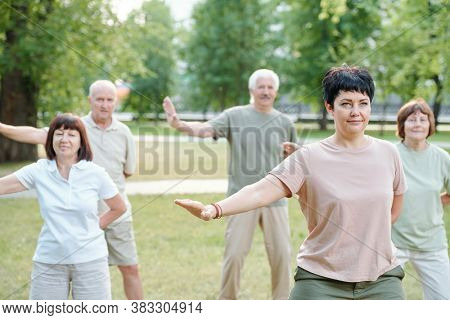 Active mature people standing in park and moving arms at qigong practice