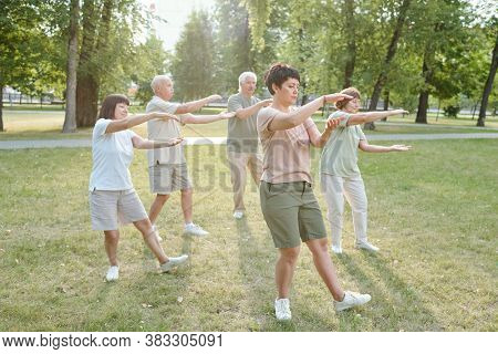 Group of focused senior people and their coach gesturing hands and doing qigong exercise in park