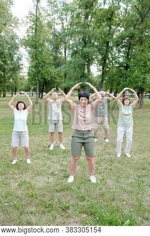 Skilled mature coach showing qigong exercise to senior students in city park
