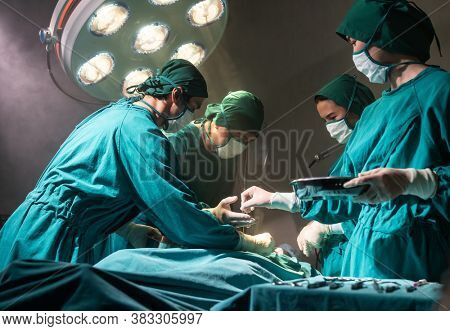 Operating room nurse send surgical equipment for surgeon doctor with Medical Team Performing Surgical Operation in Operating Room OR. Medical health care Surgery concept.
