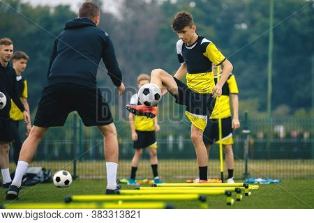 Teenagers On Soccer Training Camp. Boys Practice Football Witch Young Coaches. Junior Level Athletes