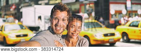 New York selfie couple taking photo on NYC city summer holiday vacation travel with yellow taxi cabs panoramic background. Man and woman tourists happy smiling.
