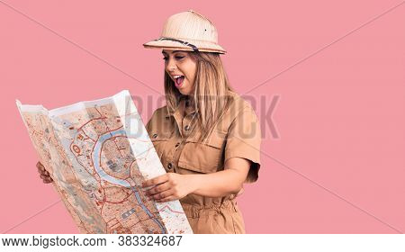 Young beautiful woman wearing explorer hat holding map looking positive and happy standing and smiling with a confident smile showing teeth