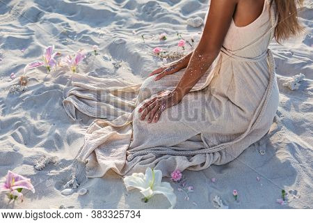 Beautiful Young Woman In Elegant White Dress Sitting On Sand At Sunset Close Up