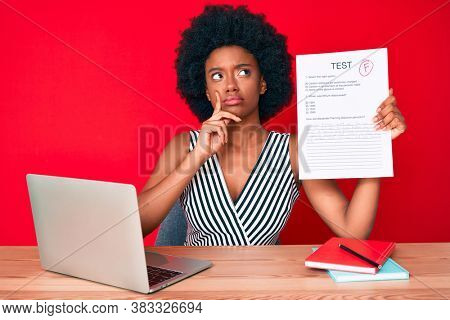 Young african american woman showing a failed exam serious face thinking about question with hand on chin, thoughtful about confusing idea