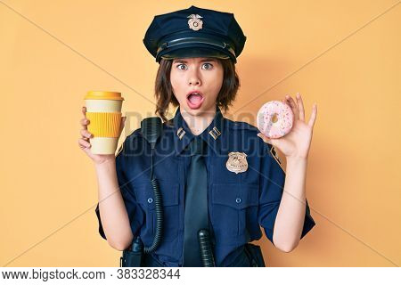 Young beautiful woman wearing police uniform holding donut and take away coffee in shock face, looking skeptical and sarcastic, surprised with open mouth