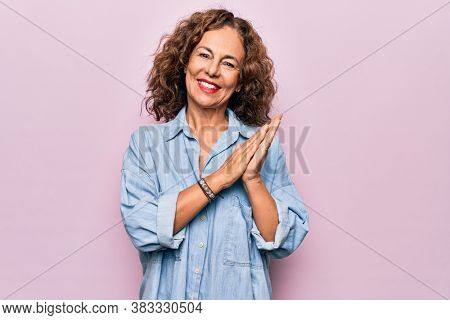 Middle age beautiful woman wearing casual denim shirt standing over pink background clapping and applauding happy and joyful, smiling proud hands together