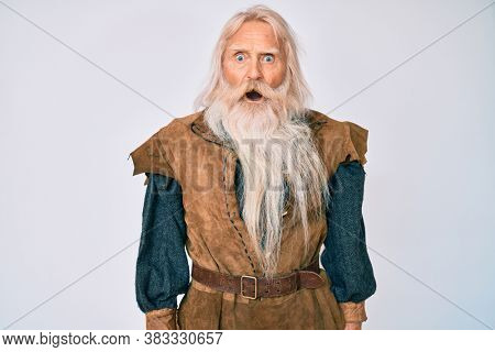 Old senior man with grey hair and long beard wearing viking traditional costume in shock face, looking skeptical and sarcastic, surprised with open mouth