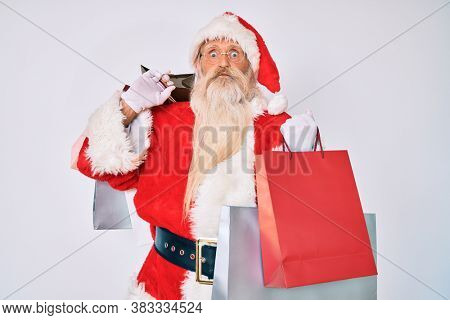 Old senior man with grey hair and long beard wearing santa claus costume holding shopping bags puffing cheeks with funny face. mouth inflated with air, catching air.
