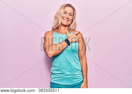 Middle age caucasian blonde woman wearing sports clothes over pink background cheerful with a smile of face pointing with hand and finger up to the side with happy and natural expression on face