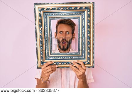 Handsome caucasian man with beard holding empty frame in shock face, looking skeptical and sarcastic, surprised with open mouth
