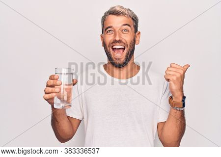 Handsome blond man with beard drinking glass of water to refreshment over white background pointing thumb up to the side smiling happy with open mouth