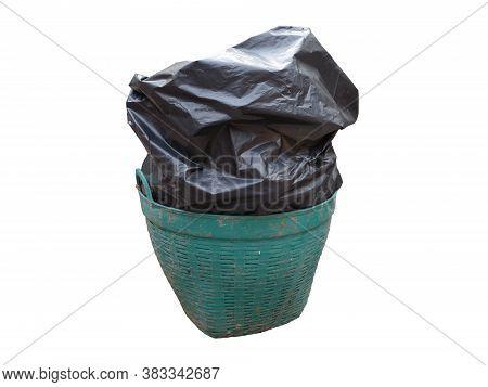 close up black garbage bag (trash bag) overflow old and grimy green plastic trash basket (garbage bin) isolated on white background