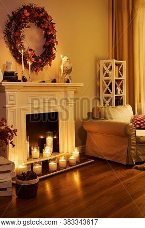 Autumn Interior. The Concept Of Family Comfort. Fireplace With Candles, Armchair In The Room Floor D
