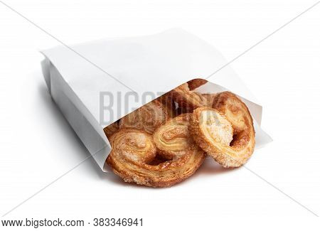 Flaky  Pastry Hearts Glazed With Caramelized Sugar In Paper Bag Isolated On White