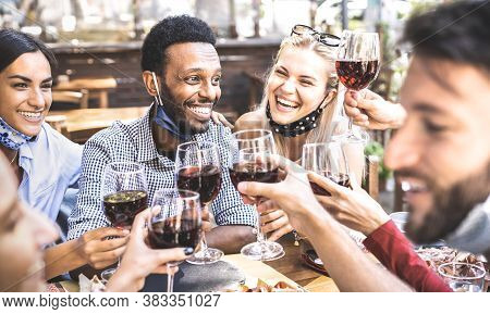Friends Toasting Red Wine At Outdoor Restaurant Bar With Open Face Mask - New Normal Lifestyle Conce