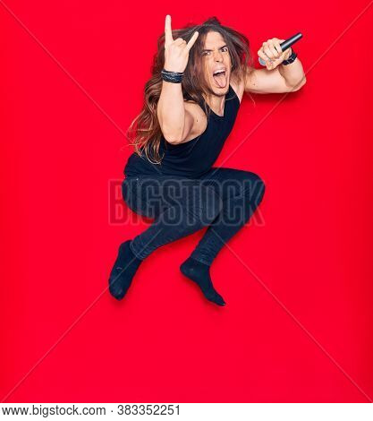 Young handsome heavy metal singer man with long hair and aggressive expression. Singing song using microphone jumping over isolated red background.