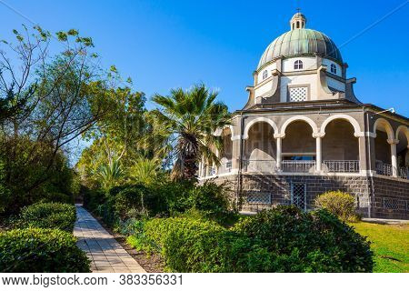 Church of the Beatitudes. The church is octagonal in honor of the eight Beatitudes. The Lake Tiberias. Blooming huge park around the monastery. The concept of religious pilgrimage and photo tourism
