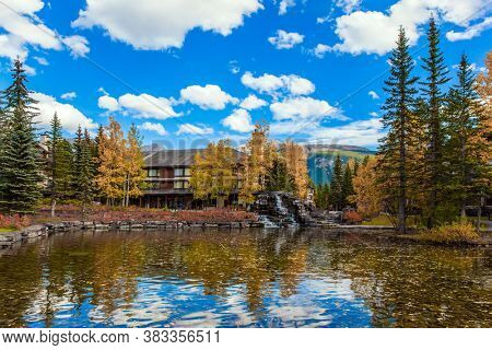 Shallow lake with yellow autumn leaves. Lush autumn in the Canadian Rockies. The valley of Kananaskis mountain park. The concept of active, ecological and photo tourism