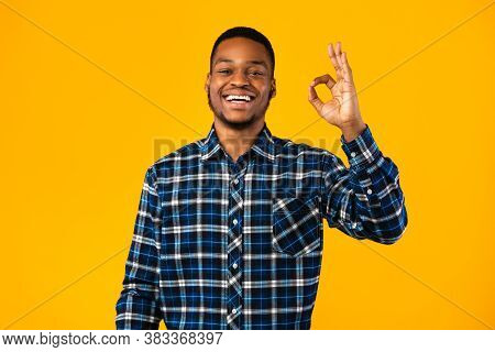 Everything Is Okay. Cheerful Black Guy Gesturing Ok Smiling To Camera Standing In Studio Over Yellow
