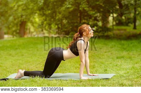 Beautiful Young Woman Doing Cat Cow Yoga Sequence On Mat At Park, Panorama