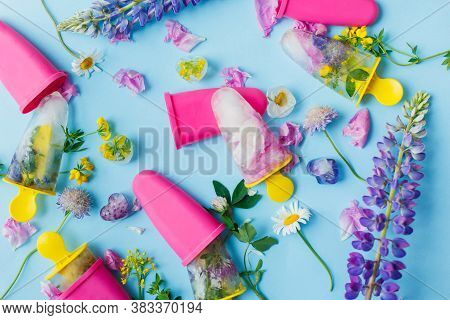 Floral Ice Pops. Colorful Wildflowers In Frozen Popsicles And Ice Cubes On Blue Background Flat Lay