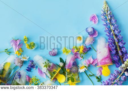 Floral Ice Pops. Frozen Popsicles And Ice Cubes Made Of Colorful Wildflowers On Blue Background With