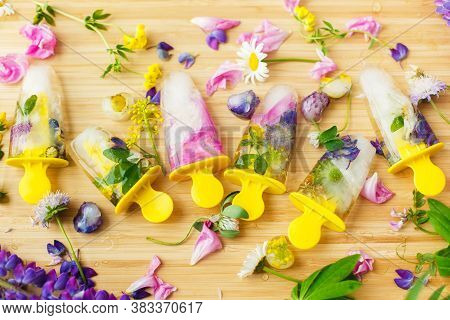 Colorful Wildflowers In Frozen Popsicles And Ice Cubes And Fresh Summer Flowers On Wooden Background