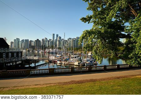 Coal Harbor Walkway Vancouver. The Vancouver skyline from the Stanley Park shoreline across Coal Harbor. British Columbia, Canada.