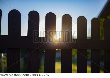 The Sun Is Shining Through The Fence. Evening In The Village. Wooden Fence Made Of Boards. Fence Aro