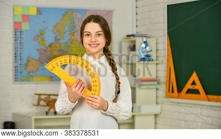 Cute Little Schoolgirl With Geometrical Tool For Mathematics. Mathematics Matters. Small Child Holdi