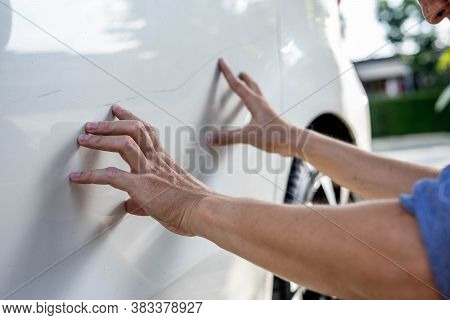 Man Checking Car Scratch Dent Damage. Car Care And Protection Concept.