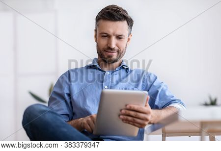 Portrait Of Handsome Young Man Using Digital Tablet During Break In Office, Browsing Internet Or Soc