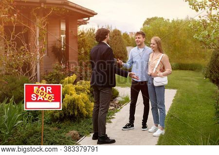 Real Estate Broker And New Home Owners In Front Of Their Property Outside