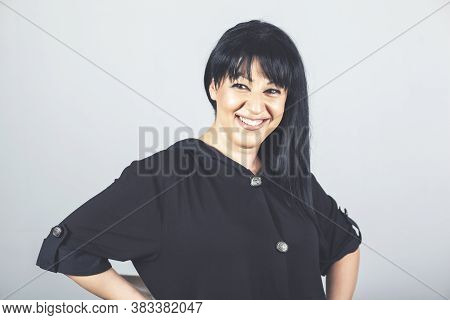Beautiful Young Happy Smiling Woman With Black Hair Posing In Studio.