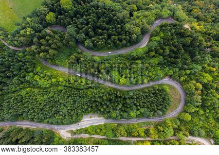 Aerial view of a winding countryside road passing through the green forest and mountain. White camping cars are passing through.