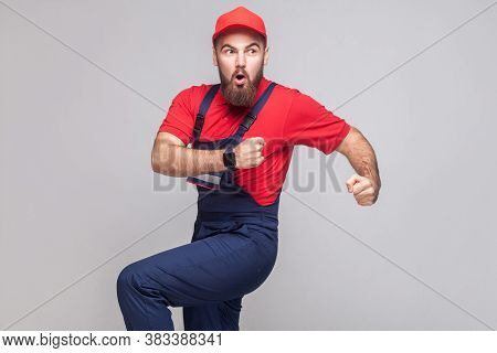 Hurry Up! Young Amazed Handyman With Beard In Blue Overall, Red T-shirt And Cap Are Late And Startin