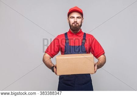 Portrait Of Young Smiling Logistic Delivery Man With Beard In Blue Uniform And Red T-shirt Standing
