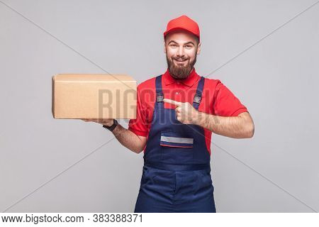 Young Cheerful Logistic Delivery Man With Beard In Blue Uniform And Red T-shirt Standing, Holding An