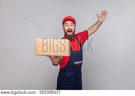 Young Happy Logistic Delivery Man With Beard In Blue Uniform And Red T-shirt Standing, Holding Cardb