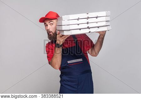 Young Playful Delivery Man With Beard In Blue Uniform And Red T-shirt Standing, Holding And Peeping
