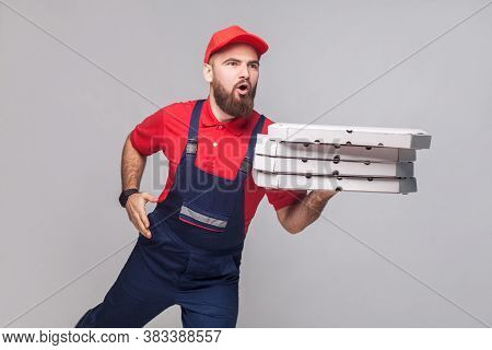 Hurry Up! Young Amazed Delivery Man With Beard In Blue Uniform And Red T-shirt Holding Stack Pizza B