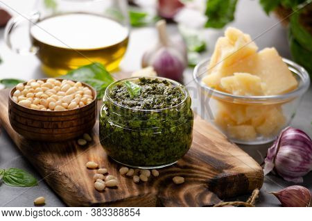 Glass Jar With Genovese Pesto Sauce On Cutting Board With Basil Leaves, Pine Nuts, Parmesan Cheese,