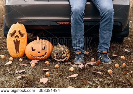 Crop View Of Adult Man Sitting In Trunk Of Car With Carved Halloween Pumpkins. Male Legs In Jeans Ne
