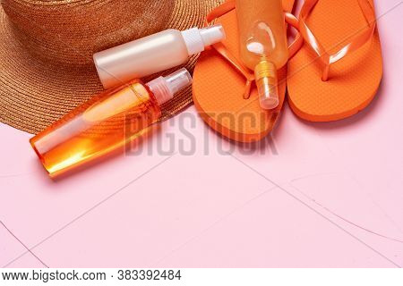 Suntan Oil Spray Bottles And Straw Hat On Pink Background