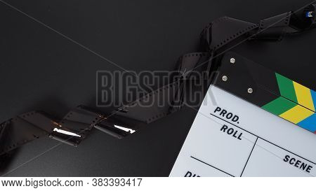Clapper Board Or Movie Slate And Film Roll. It Use In Video Production And Cinema Industry On Black